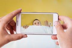 Schüchterne Manntelefonphotographie Stockbilder