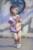 Schüchternes Kindermädchen mit Zöpfen auf einem Hintergrund einer Betonmauer mit Graffiti Lizenzfreie Stockfotografie