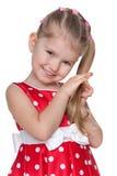 Schüchternes kleines Mädchen in einem roten Tupfenkleid Stockfotos