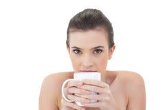 Schüchternes natürliches braunes behaartes Modell, das einen Becher Kaffee hält Stockbild