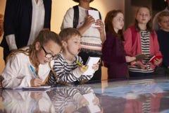 Schüler auf Reise zum Museum, das Karte betrachtet und Anmerkungen macht lizenzfreie stockfotografie
