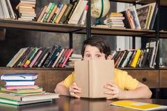 Schüler, der über Buch in der Bibliothek blickt Lizenzfreies Stockbild