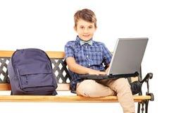 Schüler, der auf einer Holzbank mit Schultasche nahe bei ihm sitzt Stockbild