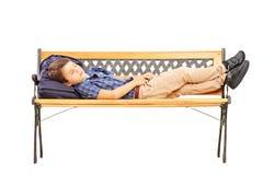 Schüler, der auf einer Holzbank schläft Lizenzfreie Stockfotografie