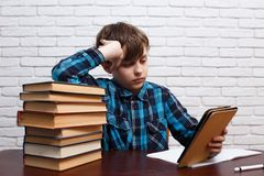 Schüler, der das elektronische Buch sitzt an der Bibliothek mit a liest lizenzfreies stockfoto
