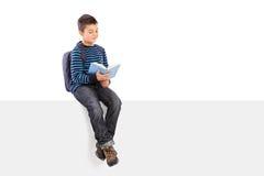 Schüler, der ein Buch gesetzt auf Schild liest Lizenzfreie Stockfotografie