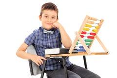 Schüler, der an einem Schreibtisch mit einem Abakus auf ihm sitzt Lizenzfreie Stockbilder