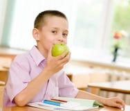 Schüler, der einen Apfel isst Lizenzfreies Stockbild