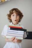 Schüler, der einen Stapel Bücher hält Stockfotos