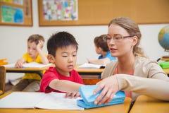 Schüler, der einen Stift in seinem Bleistiftkasten nimmt Stockbild