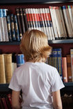 Schüler, der gegen Bücherregal in der Bibliothek steht Lizenzfreies Stockfoto