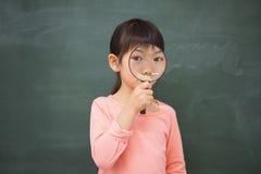 Schüler, der Kamera mit Lupe schaut Lizenzfreies Stockbild