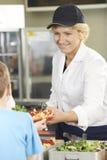 Schüler in der Schulcafeteria, die das Mittagessen von Abendessen-Dame gedient wird Stockbilder