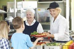 Schüler in der Schulcafeteria, die das Mittagessen von den Abendessen-Damen gedient wird Stockfotografie