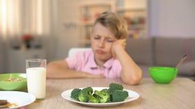 Schüler, der traurig Brokkoli auf weißer Platte, Kindheitsnahrung, Nahrung betrachtet stock footage