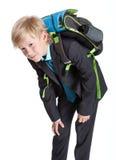 Schüler des ersten Grades in der Uniform mit schwerer Schultasche, blonder kaukasischer Junge, lokalisierter weißer Hintergrund Stockbild