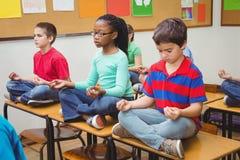 Schüler, die auf Klassenzimmerschreibtischen meditieren lizenzfreie stockbilder
