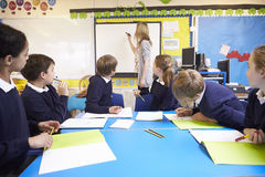 Schüler, die bei Tisch als Lehrer Stands By Whiteboard sitzen stockbild