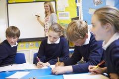 Schüler, die bei Tisch als Lehrer Stands By Whiteboard sitzen stockbilder