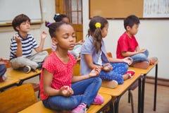 Schüler, die in Lotussitz auf Schreibtisch im Klassenzimmer meditieren lizenzfreies stockbild