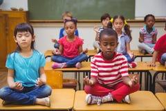 Schüler, die in Lotussitz auf Schreibtisch im Klassenzimmer meditieren lizenzfreie stockbilder