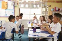 Schüler, die sich um in Lektion an der Grundschule, Seitenansicht drehen lizenzfreie stockfotos