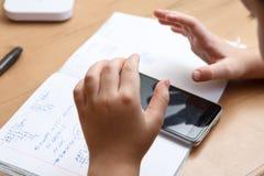 Schüler mit dem Smartphone, der zu Hause Hausarbeit tut Lizenzfreie Stockbilder