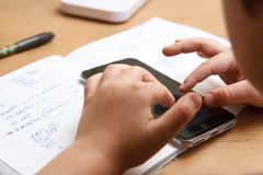 Schüler mit dem Smartphone, der zu Hause Hausarbeit tut Lizenzfreie Stockfotografie