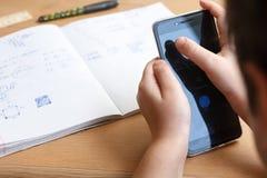 Schüler mit dem Smartphone, der zu Hause Hausarbeit tut Stockbild