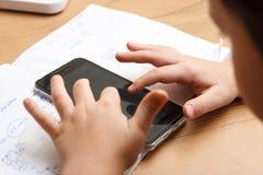 Schüler mit dem Smartphone, der zu Hause Hausarbeit tut Stockfotos