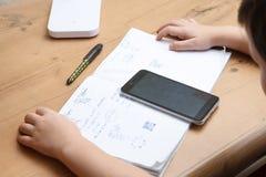 Schüler mit dem Smartphone, der zu Hause Hausarbeit tut Lizenzfreies Stockfoto