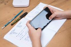 Schüler mit dem Smartphone, der zu Hause Hausarbeit tut Stockfoto
