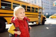 Schüler mit Schultasche mit gelbem Schulbus auf Hintergrund stockfoto