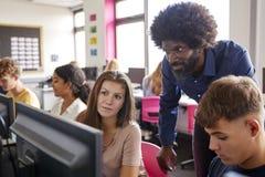 Schüler-Working In Computer-Klasse männlicher Lehrer-Helping Teenage Females hohe stockfotos