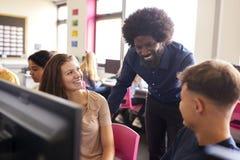 Schüler-Working In Computer-Klasse männlicher Lehrer-Helping Teenage Females hohe lizenzfreie stockbilder
