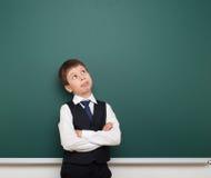Schülerjunge betrachten oben der sauberen Tafel, dem Gesichtes Verziehen Gesichtes Verziehen und den Gefühlen, gekleidet in einem Stockfotos
