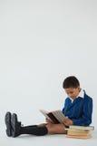 Schülerlesebuch auf weißem Hintergrund Lizenzfreie Stockfotografie