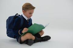 Schülerlesebuch beim Sitzen auf weißem Hintergrund Stockbild