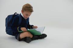 Schülerlesebuch beim Sitzen auf weißem Hintergrund Lizenzfreie Stockbilder