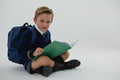 Schülerlesebuch beim Sitzen auf weißem Hintergrund Lizenzfreies Stockbild