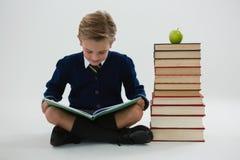 Schülerlesebuch beim Sitzen neben Buchstapel Stockfotografie