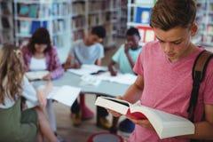 Schülerlesebuch mit seinen Mitschülern, die im Hintergrund studieren Stockfotografie