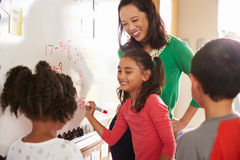 Schülerschreiben auf dem Brett an Volksschulemathe klassifizieren stockfoto