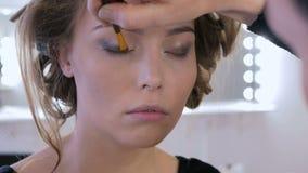 2 Schüsse Berufsmake-upkünstler, der Lidschatten anwendet stock video footage