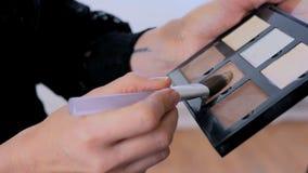2 Schüsse Berufsmake-upkünstler, der Make-up auf Frau ` s Gesicht anwendet Stockfotografie