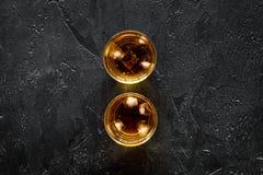 Schüsse des Whiskys mit Eis auf schwarzem Draufsichtspott des Bartischhintergrundes oben Lizenzfreie Stockfotografie