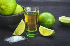 Schüsse von Goldtequila mit Kalk und Salz auf dem schwarzen Hintergrund Stockbild