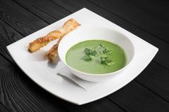 Schüssel Brokkolicremesuppe auf schwarzem hölzernem Hintergrund Stockfotos