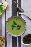 Schüssel der Brokkolicremesuppe, des Kornbrotes mit Kürbiskernen und des Löffels auf dem Tisch, gesundes vegetarisches Essenkonze stockfoto