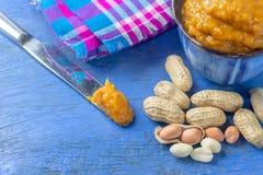 Schüssel der Erdnussbutter und des Löffels der Erdnussbutter und der Erdnüsse auf blauem hölzernem Hintergrund von der Draufsicht lizenzfreies stockbild